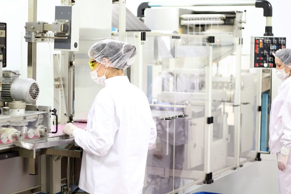 People in protective wear in a manufacturing lab